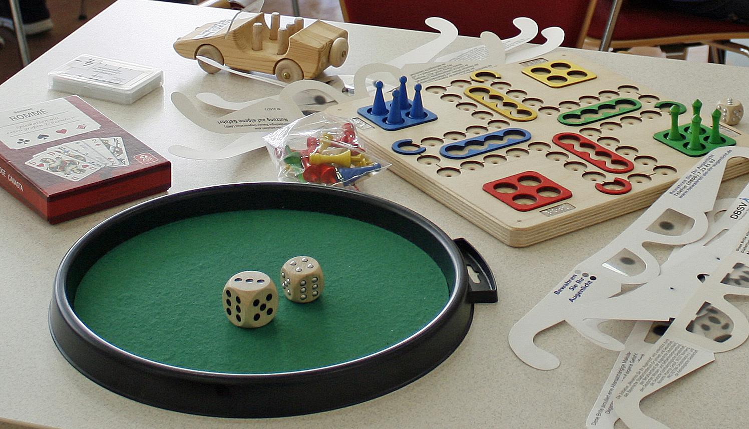 """Auf einem Tisch sind ein """"Mensch ärgere dich nicht"""" für blinden Menschen, Würfel mit taktilen Punkten und ein Kartenspiel"""