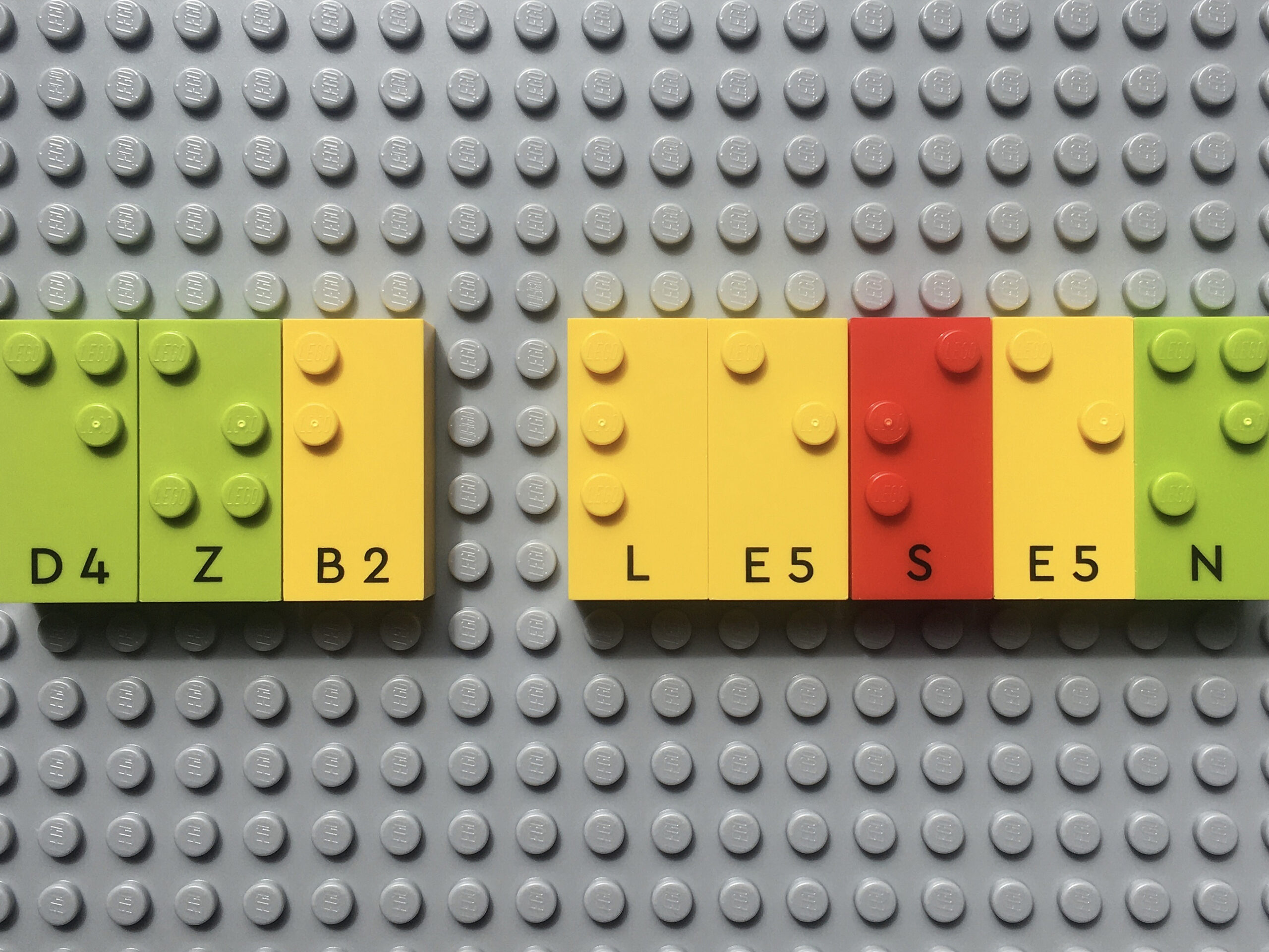 LEGO Braillesteine (oben Brailleschrift als Noppen, unten Schwarzschrift) auf Grundplatte. Es sind die Wörter dzb lesen gelegt.